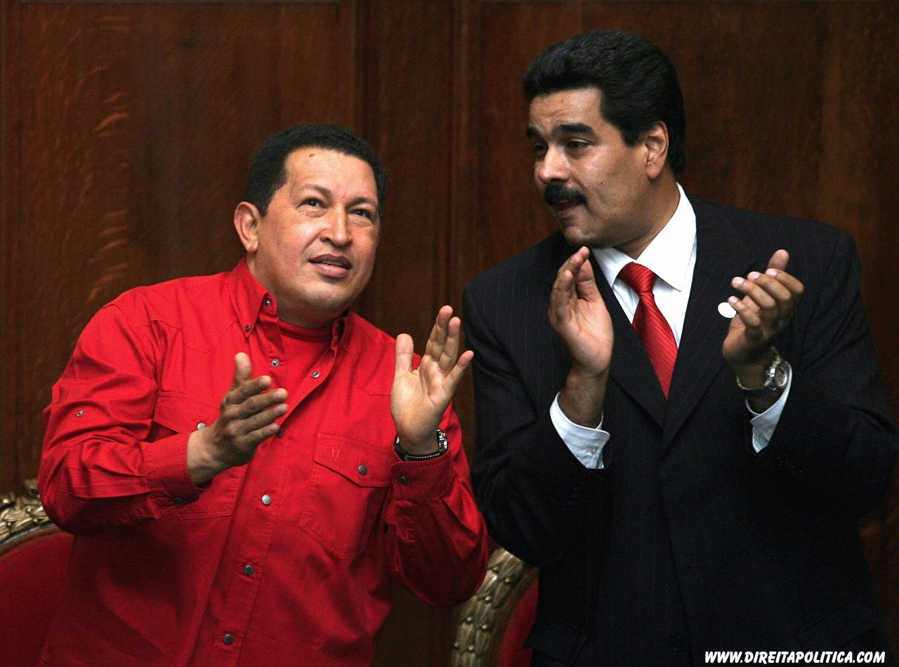 Venezuelan President Hugo Chavez (L) and Venezuelan Minister of Foreign Affairs Nicolas Maduro applaud during the ceremony in which Uruguayan writer Mario Benedetti (out of frame) was decorated for his professional carreer, 18 December 2007, at the University building in Montevideo. Chavez was in Uruguay for the XXXIV Mercosur Heads of State Summit, which took place earlier on Tuesday. AFP PHOTO/Miguel ROJO (Photo credit should read MIGUEL ROJO/AFP/Getty Images)